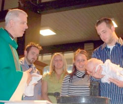 Fr. Mark Brewer Baptises a Child